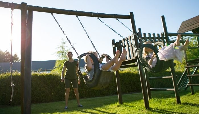 Kids swinging on playset
